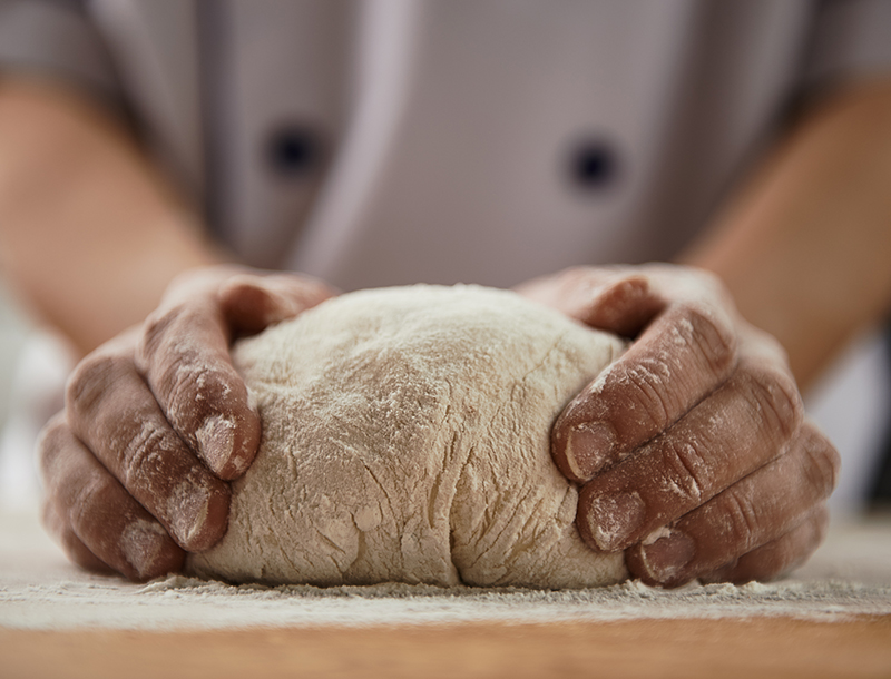 a lump of dough on a table covered in flour, while being tocuhed by two hands