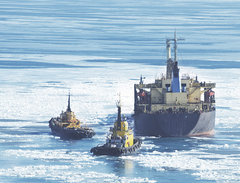 a freightship is being followed by two tugboats through icy waters